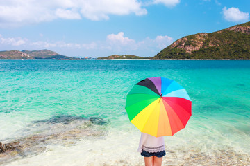 girl with color full umbrella on the sandy beach