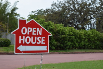 Real estate open house sign in yard of nice neighborhood.