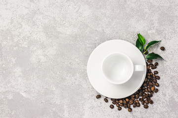 Empty white cup and coffee beans on concrete background. Top view, space for text.