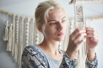 Macrame. Women's hobby. The girl mistress during work