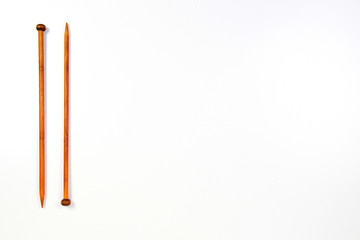 A pair of wooden knitting needles on white background.