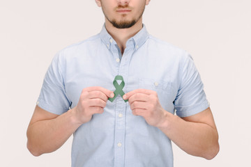 partial view of man with green ribbon isolated on white, world health day concept