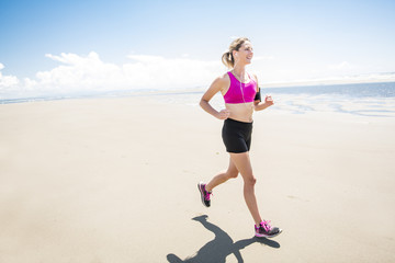 Young woman jogging on the beach in summer day. Athlete runner exercising actively in sunny day