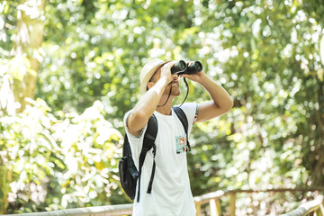 Tourists man with Binoculars Looking for something along the forest