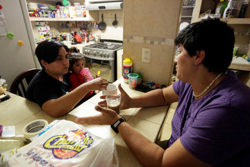 LGBT activist Jennifer Aguayo and her wife Nadia Garza, holding one of their daughters, chat at their home in Monterrey
