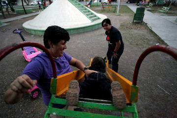 LGBT activist Jennifer Aguayo and her wife Nadia Garza play with one of their children at a park in Monterrey
