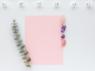 Amethyst and Rose Quartz Healing Crystals on White Background with Blank Pink Poster, Eucalyptus and Silver Globe Lights