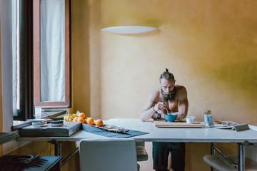 waist up young bearded man indoor preparing breakfast