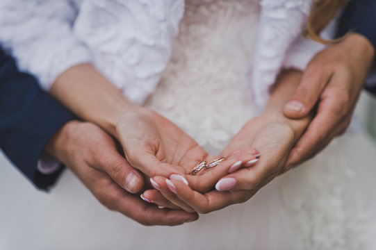 The husband embraces the brides hands with wedding rings 756.