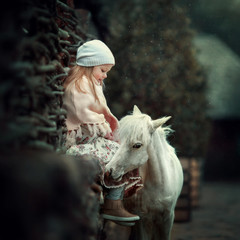 a little girl with a mini horse