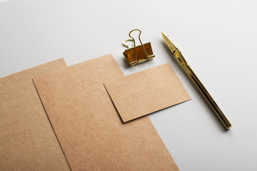 Top view of cards, business card in brown color with clip and golden pen on gray background. Mockup.