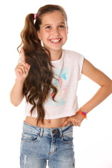 Portrait of happy slender cheerful teenage girl. The child elegantly poses makes funny faces and smiles. Young fashionista in blue jeans and with a bare belly.