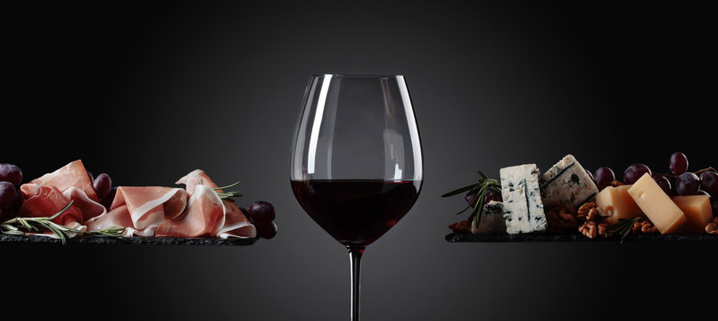 Glass of red wine with various cheeses , grapes and prosciutto .