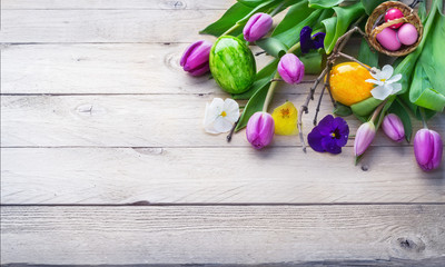 Easter background, spring flowers and colorful Easter eggs on wood