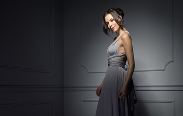 Beautiful female model wear evening dress and posing in stylish room Wall mural