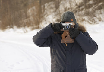 The man is taking pictures outdoors in a park. The retro photo camera is in male hands. The European is on a walk in winter jacket. It is photographing in nature.