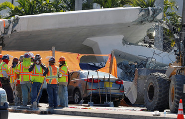 Workers prepare to remove debris from a collapsed pedestrian bridge at Florida International University in Miami