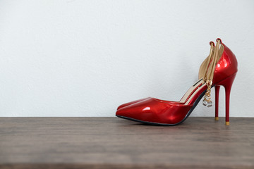 Red high heel women shoes on wooden table and white concrete background.
