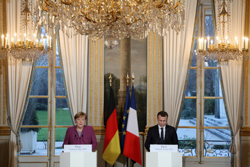 French President Emmanuel Macron and German Chancellor Angela Merkel give a joint press conference at the Eylsee presidential Palace in Paris