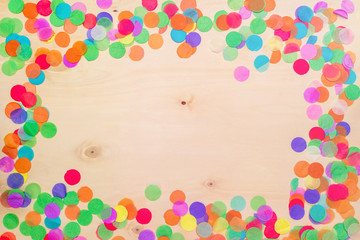 Colorful confetti on wooden background from above