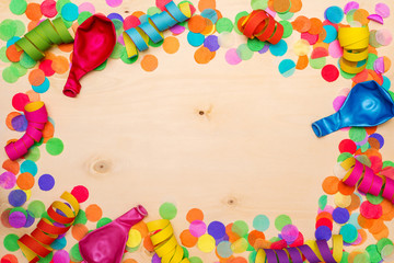 Colorful confetti and streamer on wooden background from above