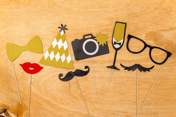 Colorful party decoration used for funny photographs on wooden background from above