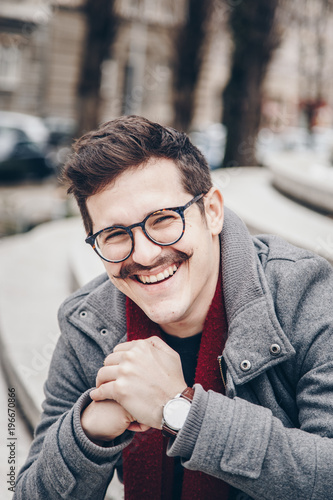 10d27ad43 fashion portrait of a attractive hipster man outside. handsome guy with a vintage  mustache, eyeglasses and a wristwatch.