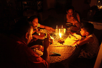 Lisney Albornoz and her family uses a candle to illuminate the table while they dine, during a blackout in San Cristobal