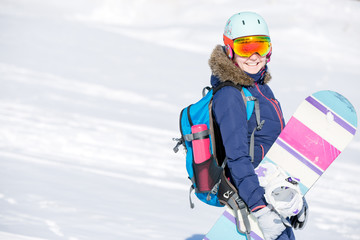 Image of female athlete wearing helmet with backpack and snowboard
