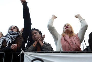 People react as they attend a gathering to protest against the death of a street hawker in central Madrid