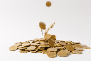 Close up of gold coins fall from above in a large pile isolated on white background. Concept of money business growth gain success earnings. Copy space for advertisement.