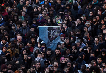 People attend a gathering to protest against the death of a street hawker in central Madrid