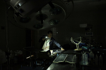 A nurse uses light from a phone while he looks for material in an out-of-use operating room of the Padre Justo hospital, during a blackout in Rubio