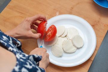 woman preparing salad of tomatoes and buffalo cheese