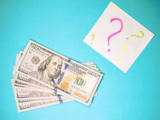 on what to spend earned money, Dollars, white paper with question marks