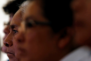 Relative of the 43 students of Ayotzinapa looks on next to others as they take part in a news conference in Mexico City