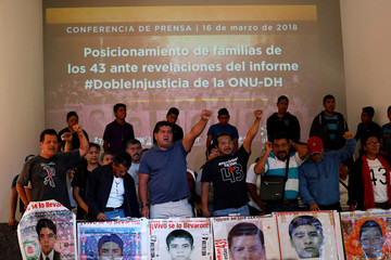 Relatives of the 43 students of Ayotzinapa shout slogans during a news conference in Mexico City