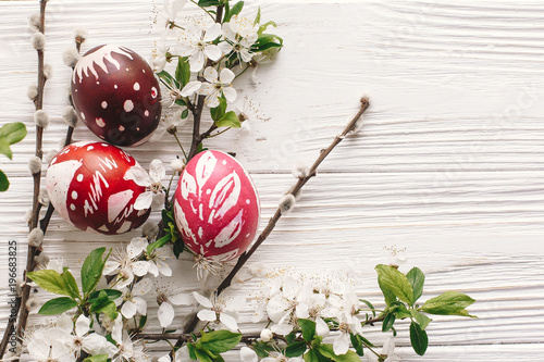 Stylish Painted Easter Eggs On Rustic Wooden Background With Spring Flowers And Willow Branches Happy