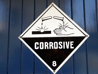 A sign warning care to be taken because the area has corrosive chemicals present