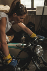 Young female working on restoration of old /vintage motorbikes in old rusty motorbike garage/workshop