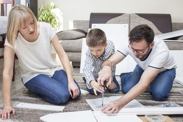 Fototapeta Rodzina skręca meble w salonie na dywanie. Ojciec wkręca śrubę wkrętakiem a mama i dziecko przyglądają się pracy.  obraz