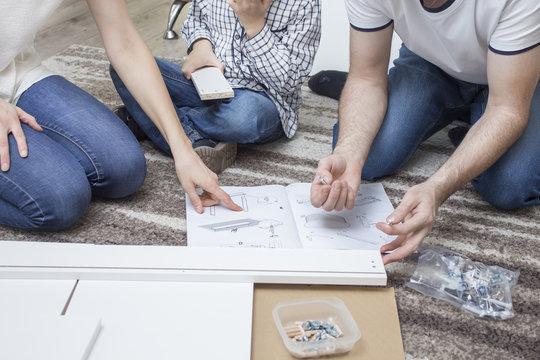 Rodzina klęczy na beżowym dywanie. Przed nimi leży instrukcja montażu mebli, którą czytają z wielką uwagą.