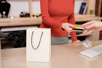 Young cashier with credit card