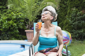 Cool senior woman drinking a cocktail in the garden