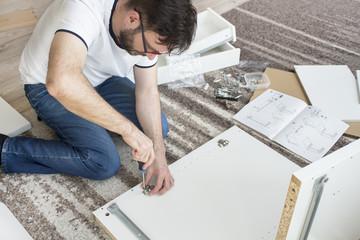 Brodaty mężczyzna w okularach, białej podkoszulce i jeansach siedzi na dywanie w salonie i skręca meble. Trzyma wkrętak i wkręca zawias.