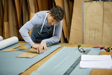 Worker Using Cardboard To Mark On Fabric In Sofa Workshop