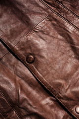 Leather texture close-up with a button. Part of a leather jacket.