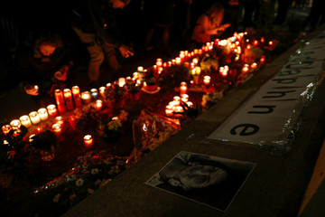 People place candles at a memorial for anti-corruption journalist Daphne Caruana Galizia in Valletta