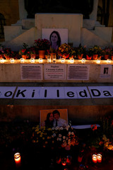 Photos of assassinated Maltese journalist Daphne Caruana Galizia and Slovak journalist Jan Kuciak and his fiancee Martina Kusnirova are seen on a makeshift memorial to Caruana Galizia in Valletta