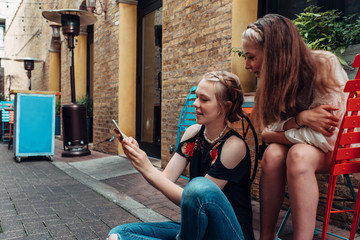 Two teenage girls checking a smartphone